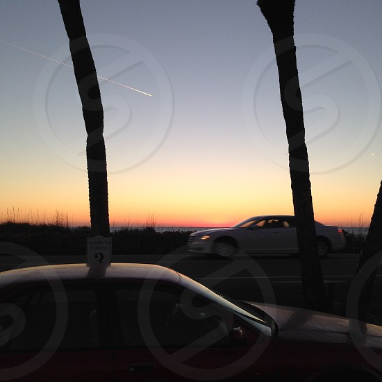 Skywriter shooting star crosses between two palm trees on a busy Florida road at dusk. Takes place during sunset and twilight. Subtle ocean views. Cars are in shadow. photo