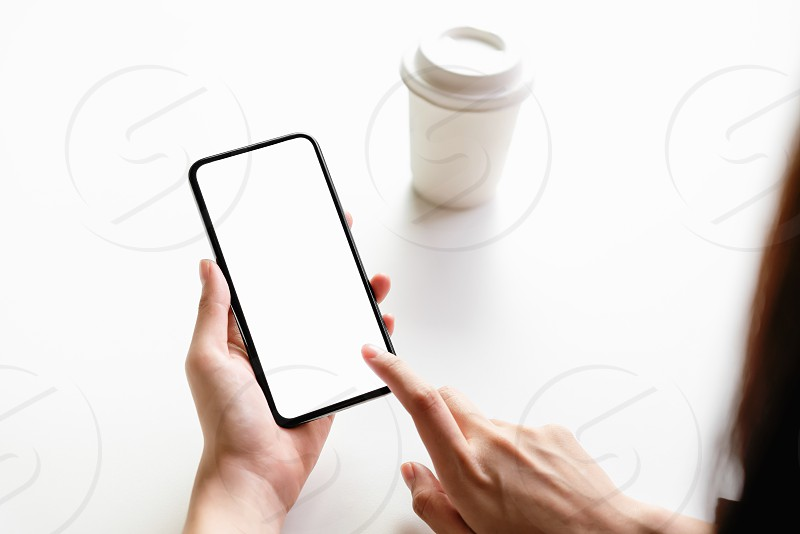 Woman holding smartphone mockup of blank screen on the table. photo