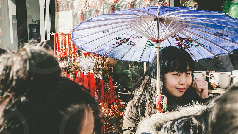 smiling dark haired woman in brown coat holding blue and pink floral parasol overhead next to outdoor market stand with hanging red charms and white bowls with people walking by photo