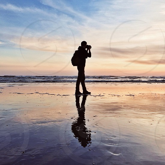 person standing on wet beach taking photo photo