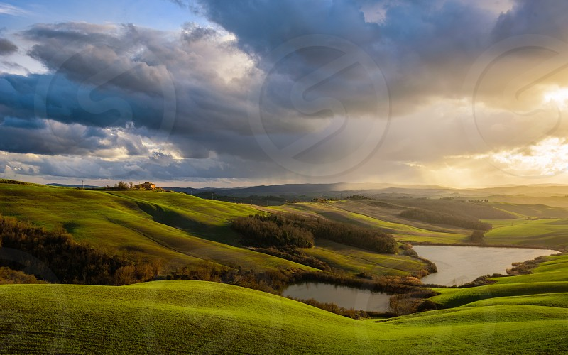 Siena tuscany Italy travel scenic view sunset clouds water rolling hills landscape dreamy peaceful countryside green lake nature photo