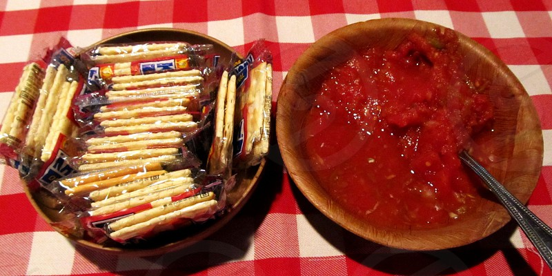 Salsa and crackers in bowls on red and white checkered tablecloth photo
