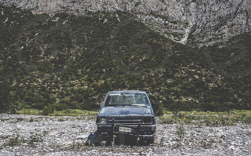 An abandoned car in the middle of the valley far away from streets. photo