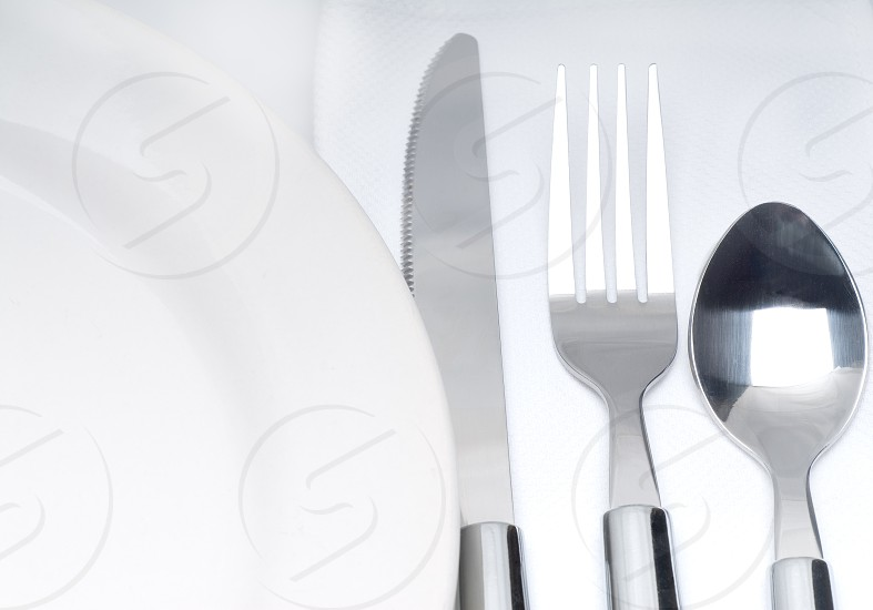 close up of a cutlery set on a table with napkin and dish photo