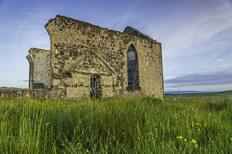 Abandoned church surrounded by lush grass and wild flowers. photo