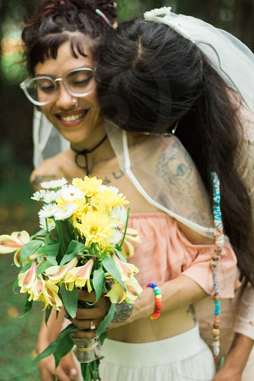 Two brides laughing and enjoying each other on their wedding day. photo