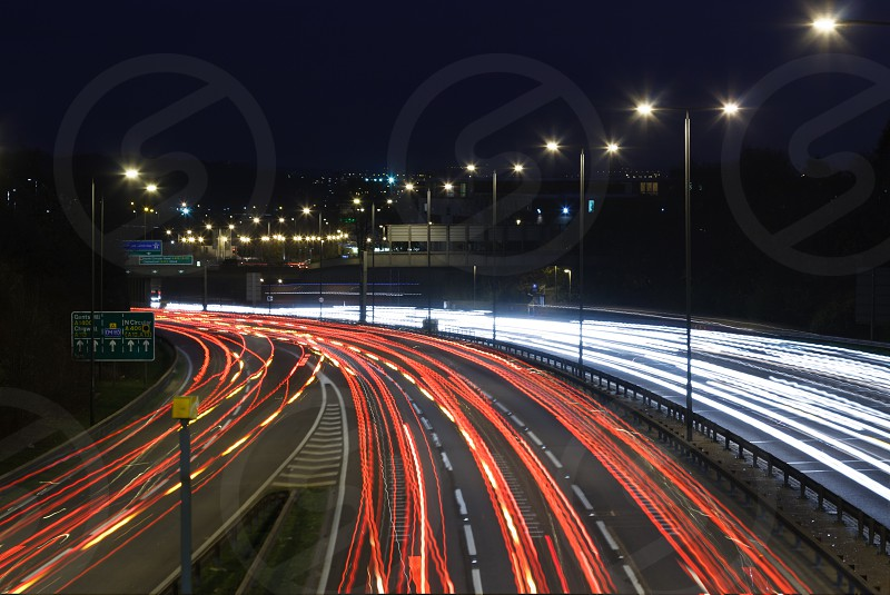 A 30 sec exposure photo taken by night over a busy motorway not far from London (probably the M11) showing white and red light trails left by car. photo