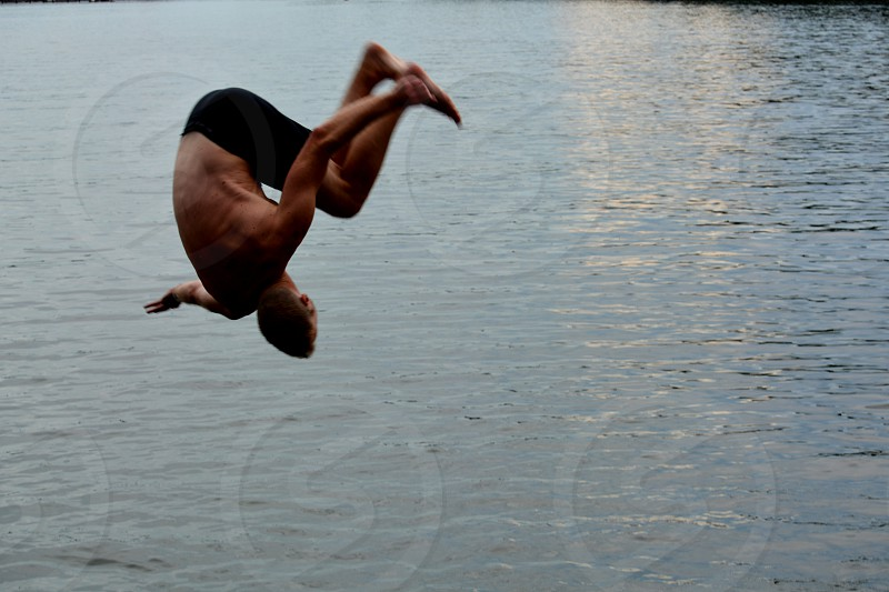Young male flipping into a lake photo