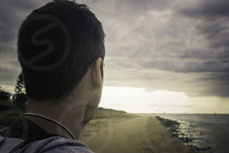 Young adult man standing in the sand on the seashore photo