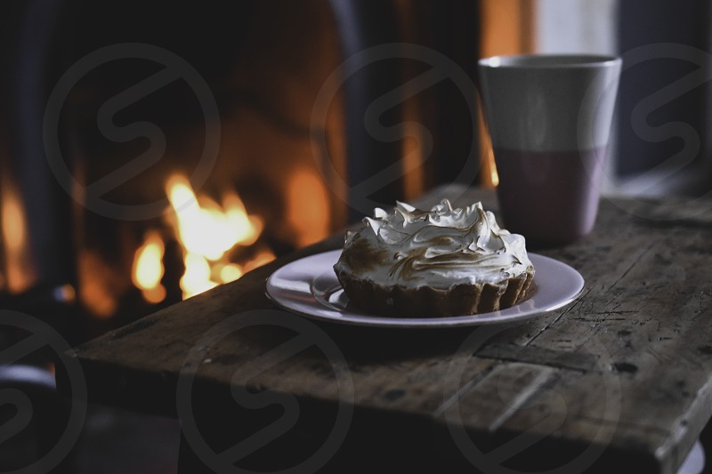 Close up of a wooden stool with a hot drink and cake by the fireplace. photo