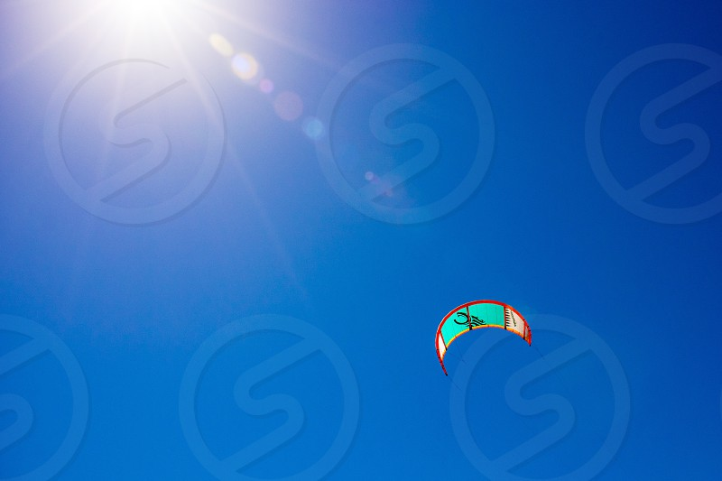 view of blue skies and man in a parachute photo