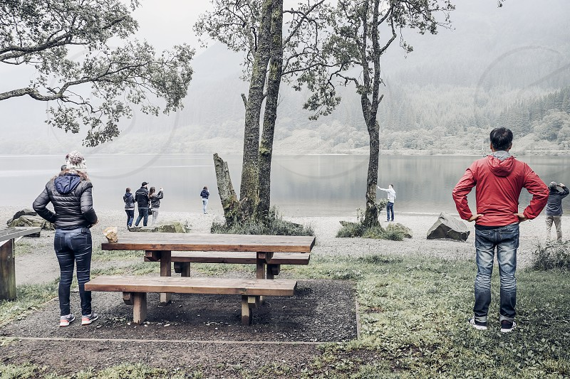 Rear view of holiday makers at misty lakeside photo
