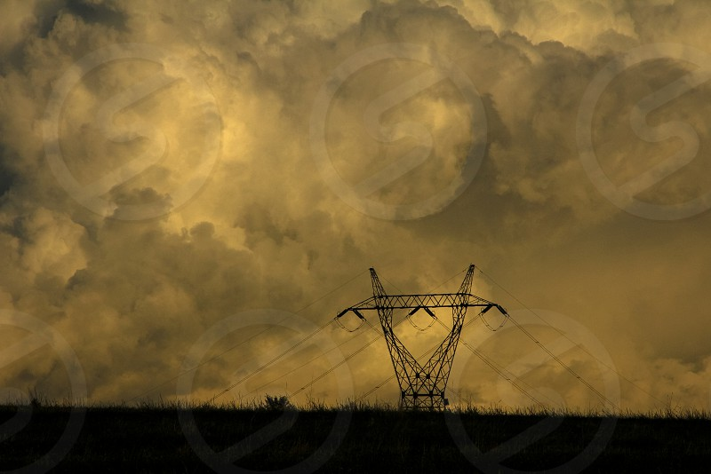 Electrical pylon is dwarfed by a massive cloud at sunset in the Brkini hills of south central Slovenia. photo
