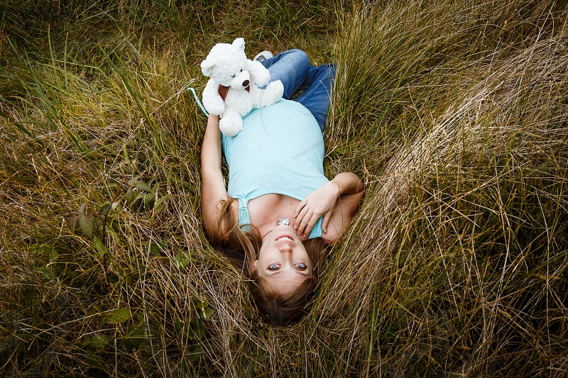 Shot of a pregnant woman lying in the grass holding a teddy bear. photo
