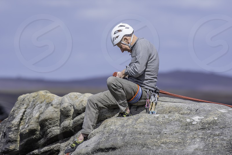 08.01.2018.Stanage EdgeDerbyshireUk.Active senior.Mature rock climber sitting on top of cliff assecurating his climbing partner from above.Blurred landscape in background. photo
