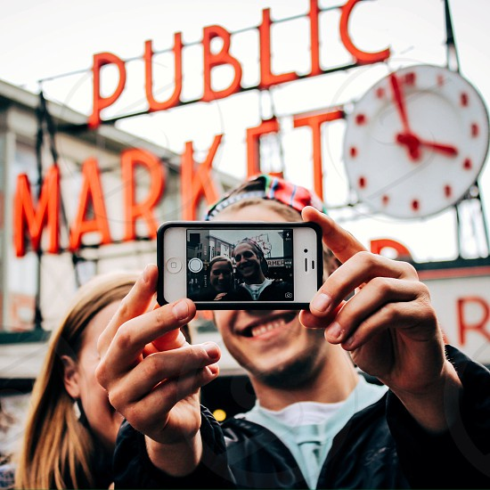 man and woman taking picture with public market photo
