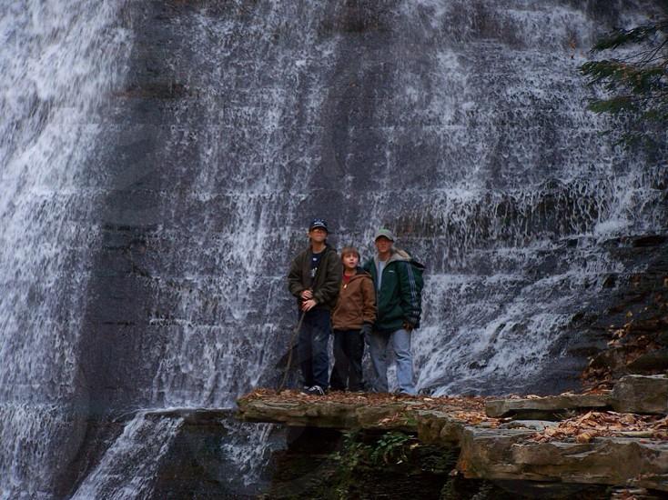 boy standing between two men beside waterfalls photo