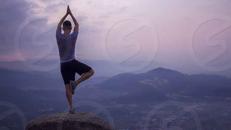man practicing yoga tree pose in the mountain photo