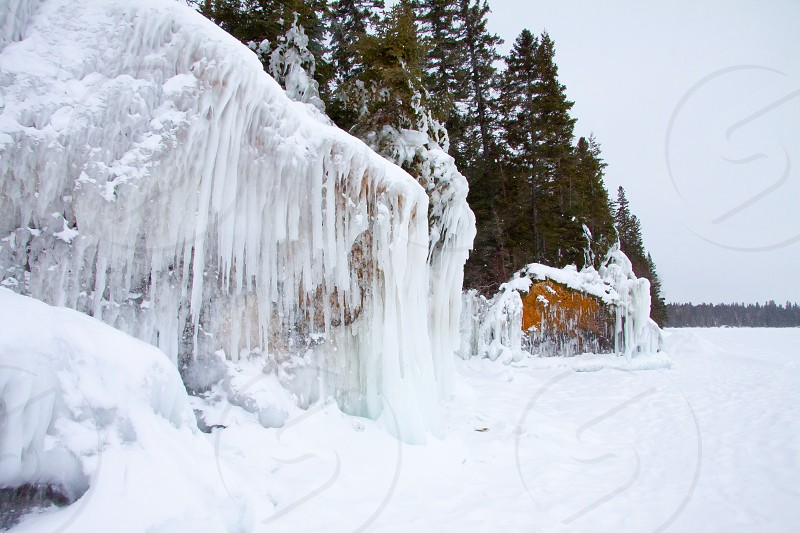 Ice  icicle  lake  northern manitoba . Canada . Rock  boulders. Snow. Winter  frozen   photo