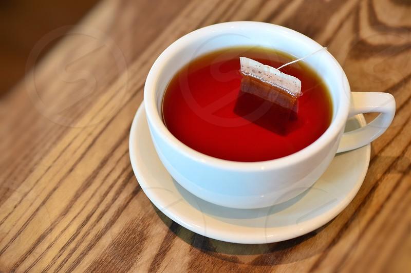 tea bag on white mug on top of saucer photo