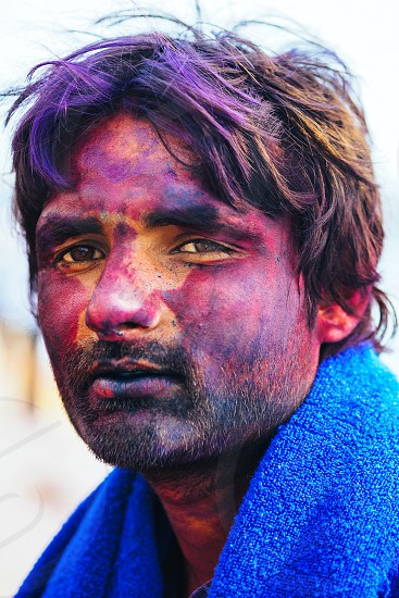 man in blue shirt with yellow purple and red painted face photo