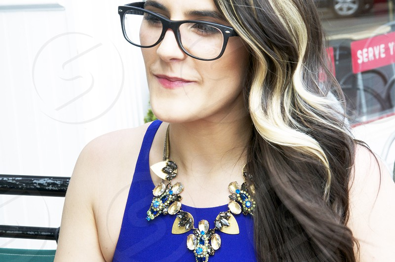 women sitting in outdoor cafe woman smiling woman with glasses & necklace pretty female with red lips beautiful young classy lady highlighted hair photo