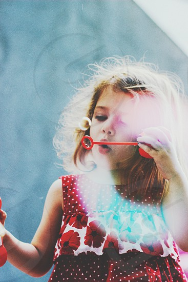 girl in red and white floral dress  playing bubbles photo