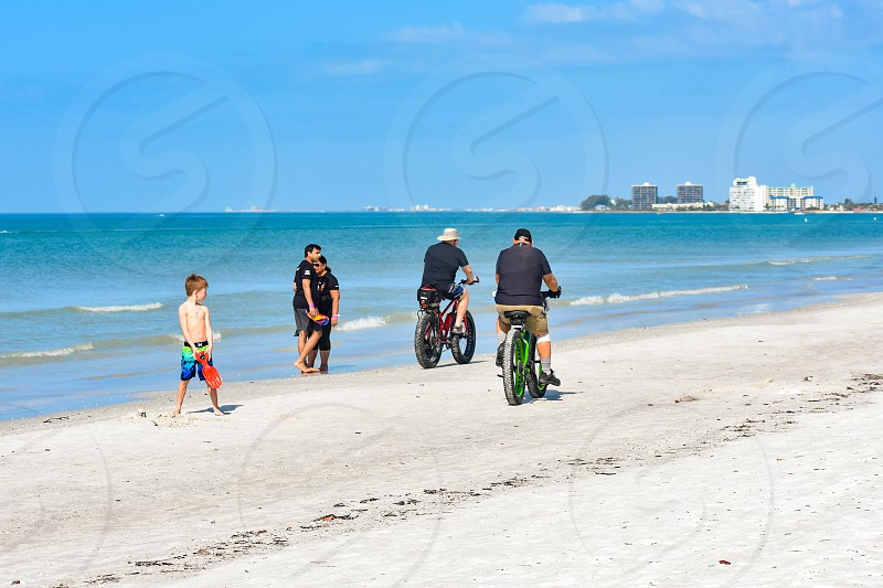 St. Pete Beach Florida. January 25 2019.  Child playing on the beach watching people ride a bicycle photo