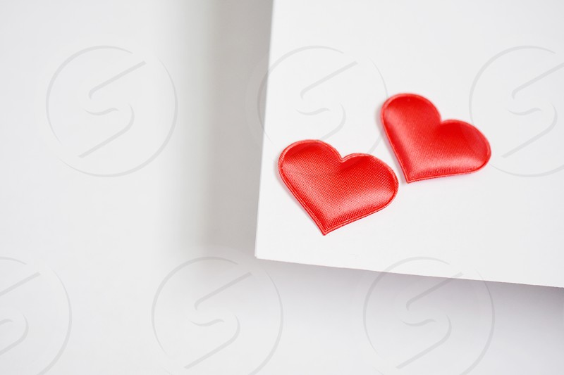 2 red heart sticker in a white printer paper photo