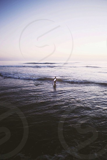 surfer in a black wetsuit carrying a white surfboard into the water with waves photo