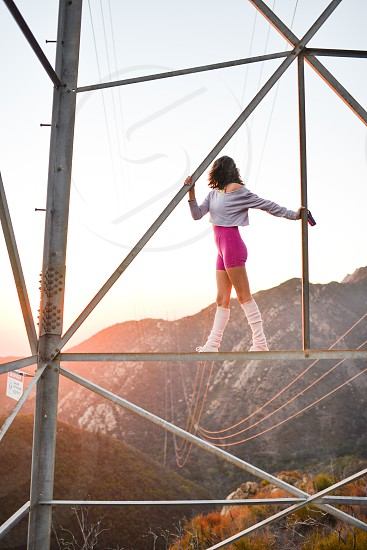 workout climbing woman girl sunset electrical tower power lines 80s clothes photo