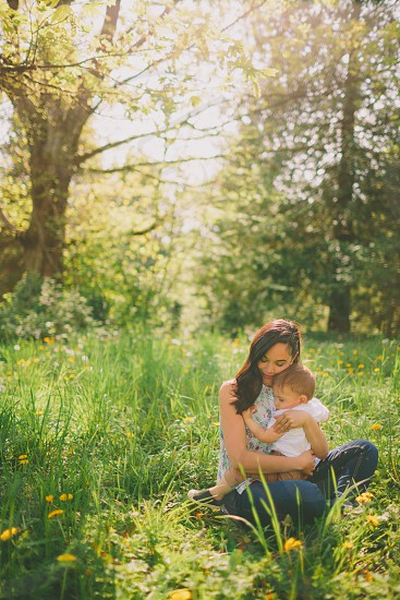 A mother holding her baby closely in a field on a sunny day.  photo