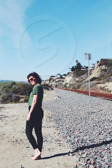 a woman wearing green blouse walking on the rocks beside the road photo
