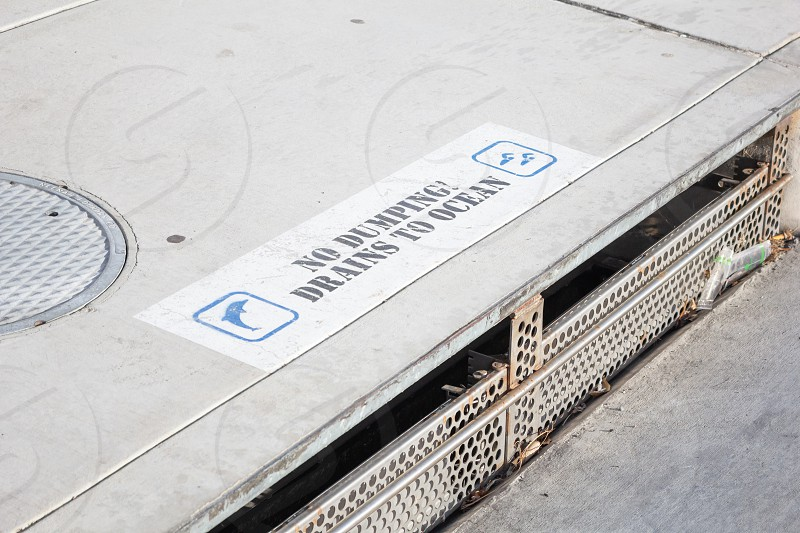 A view of a rain gutter along the street edge featuring a spray painted sign that says No Dumping Drains To Ocean. photo