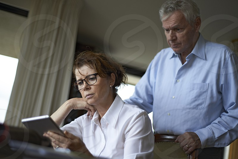 Elderly woman sitting at her dinner table in her home with a mobile phone in her hand looking upset with her husband standing behind her giving her comfort photo