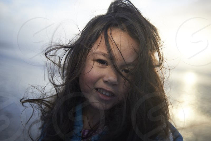 Portrait of a cute little girl happily smiling into camera whilst at the beach during sunset with her hair blowing in the wind and lookingmessy photo
