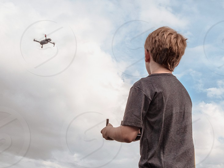 A boy flying a drone with a remote.  photo