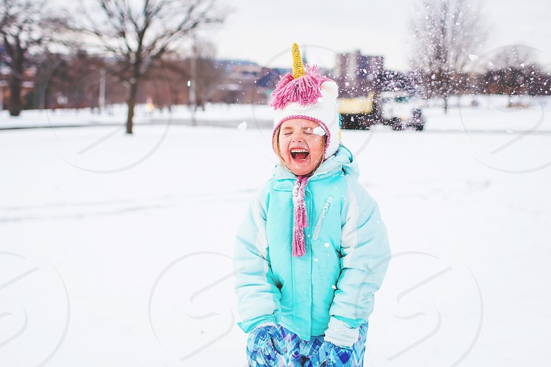 girl having fun wearing a unicorn hat in the snow during the winter photo