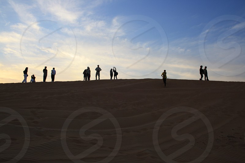 people standing on sand photography photo