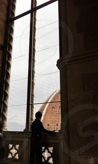 man standing beside window silhouette  photo