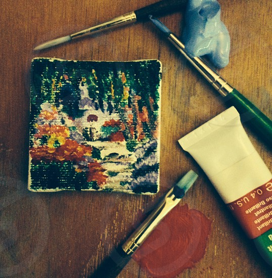 paintbrushes and tubes beside square shaped canvas with painting photo