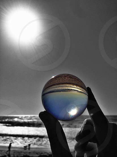 person holding a clear marble with an inverted view image photo