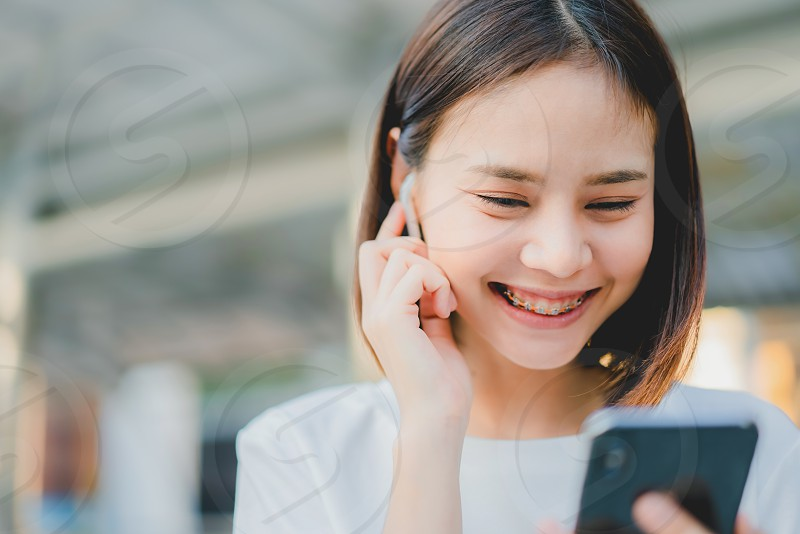 Asian women of happy smiling are listening to music from white headphones. And using hands touch to use various functions happy mood.  photo