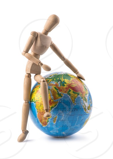 Figurine of a man trying to sit on globe photo