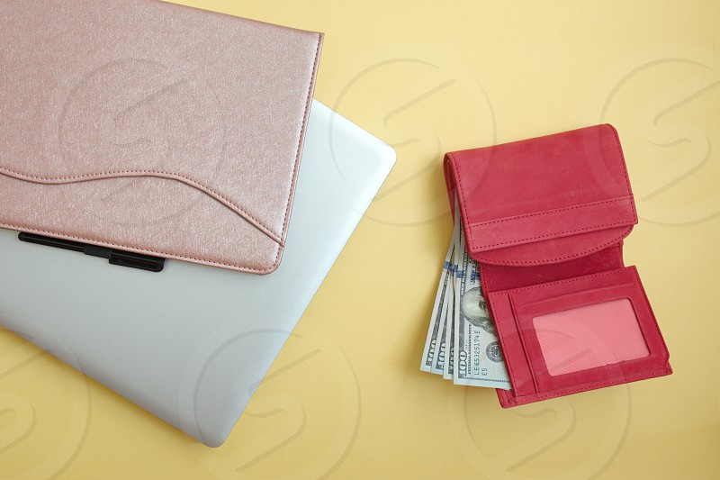 Red wallet with dollar banknotes tablet and laptop against the yellow background photo