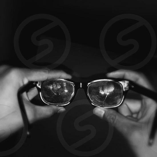 black and white photo of person holding eyeglasses photo