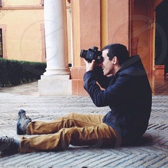 man siting on grey floor while taking picture photo