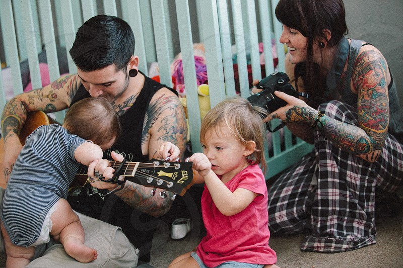 couple with tattoos sitting on floor with 2 children photo