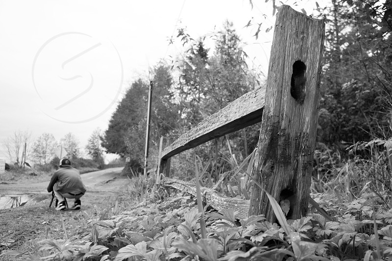 grayscale photography of a wooden fence with man setting tripod near body of water photo