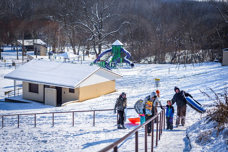 Group of people walking up stairs at a park in the snow to go sledding. photo
